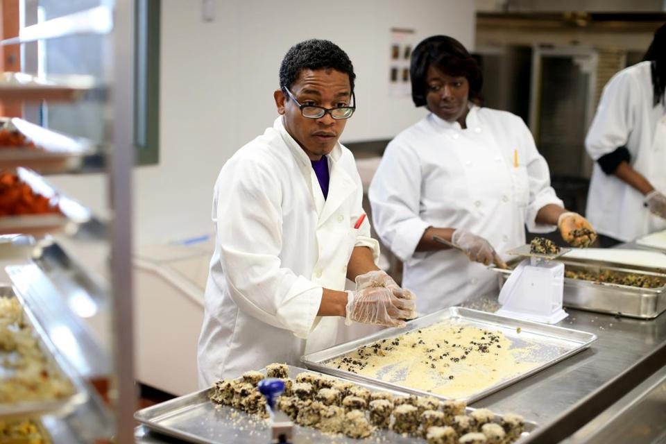 Executive chef Ismail Samad (left) and other workers prepared food in the Daily Table's Dorchester kitchen.